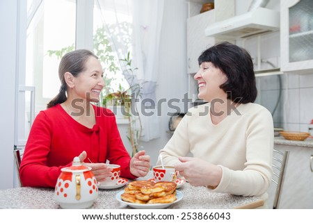 Happy mature women talking over coffee in kitchen.