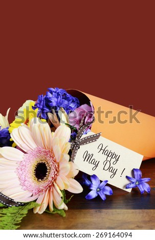 Happy May Day traditional gift of Spring Flowers in orange paper cone on dark wood table.