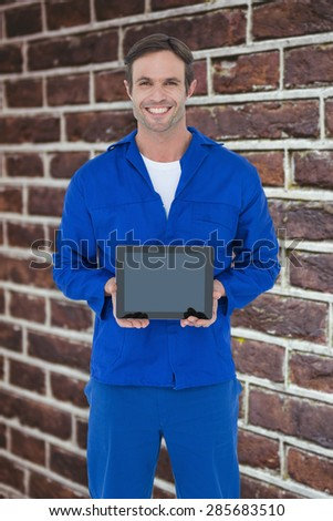 Happy mechanic holding digital tablet against red brick wall - stock photo