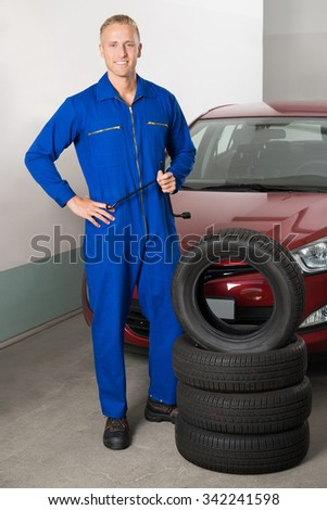 Happy Mechanic Holding Wrench Standing Besides Stack Of Tires