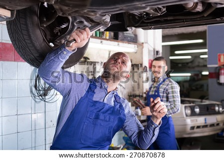 happy mechanics fixing car tire leak  - stock photo