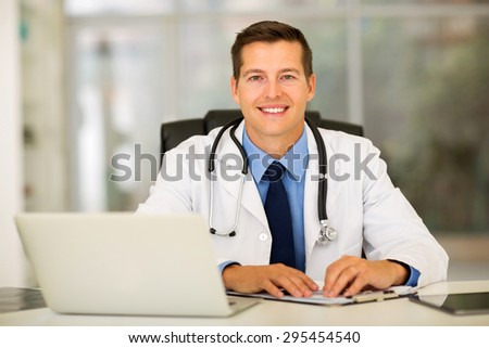 happy medical intern doctor sitting in office - stock photo
