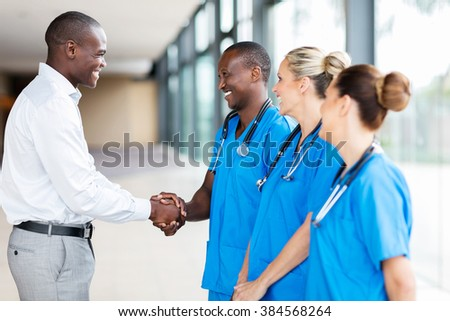 happy medical rep handshaking with group of doctors in hospital - stock photo