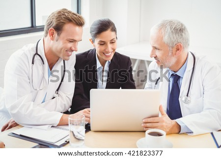 Happy medical team using laptop in conference room in hospital