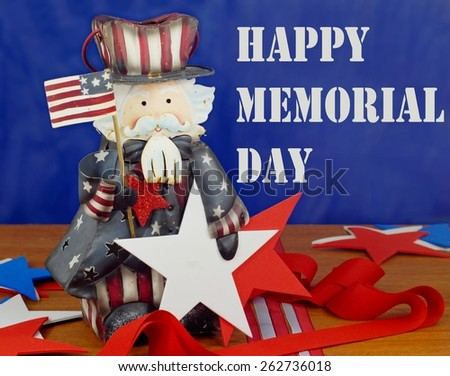 Happy Memorial Day message image in red, white and blue. A cute Uncle Sam figurine is surrounded by stars and strips with ribbons and cutouts on a wood table. Background is blue, text is white stencil - stock photo
