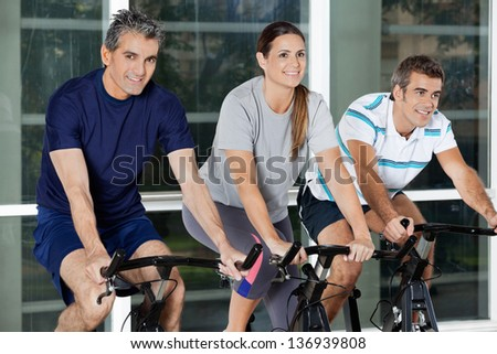 Happy men and woman on exercise bikes in health club
