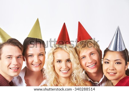 Happy men and women in birthday caps looking at camera