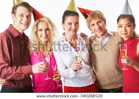 Happy men and women with champagne wearing birthday caps - stock photo