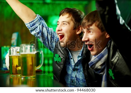 Happy men shouting while watching football match broadcast in pub - stock photo