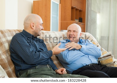 Happy men talking on the couch at home - stock photo