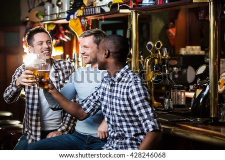 Happy men with beer in bar - stock photo