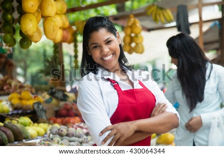 Happy mexican saleswoman on a farmers market - stock photo