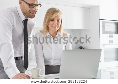 Happy mid adult business couple using laptop at kitchen counter - stock photo