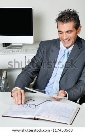 Happy mid adult businessman looking at digital tablet in office - stock photo