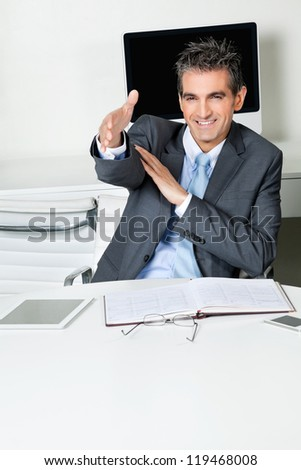 Happy mid adult businessman offering handshake while sitting at desk in office - stock photo