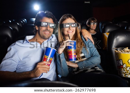 Happy mid adult couple having drinks while watching 3D film in movie theater - stock photo