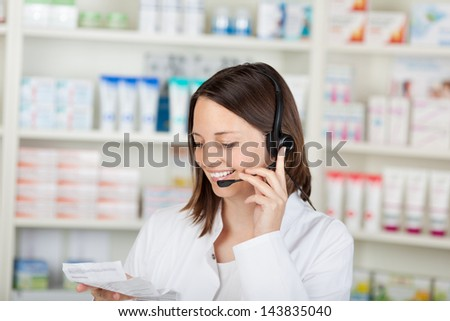 Happy mid adult female pharmacist conversing on headset in pharmacy - stock photo
