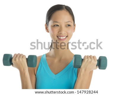 Happy mid adult woman looking away while lifting dumbbells against white background