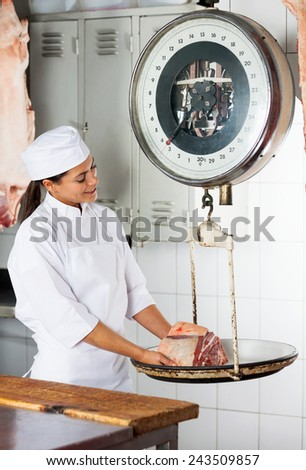 Happy mid adult woman weighing meat on scale at butchery