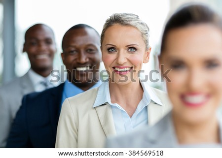 happy mid age businesswoman standing in a row with business team - stock photo