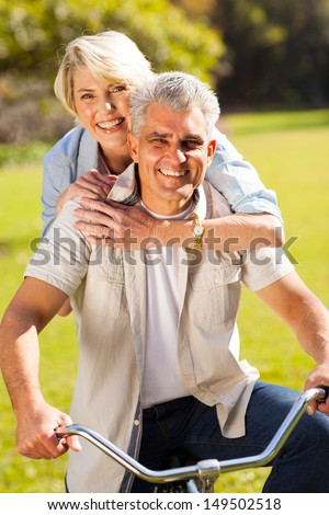 happy mid age couple on one bike outdoors