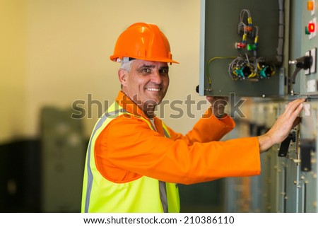 happy mid age electrician checking industrial control box - stock photo