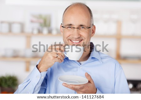 Happy mid age man drinking coffee at home - stock photo