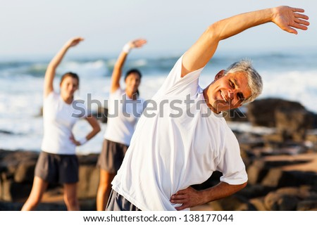 happy mid age man exercising at the beach with his family - stock photo