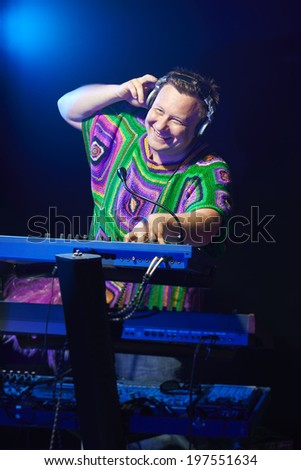 Happy mid age musician playing on a keyboard at a concert - stock photo