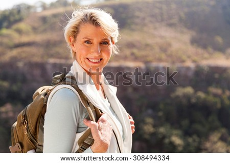 happy mid age woman with backpack standing on top of the mountain - stock photo