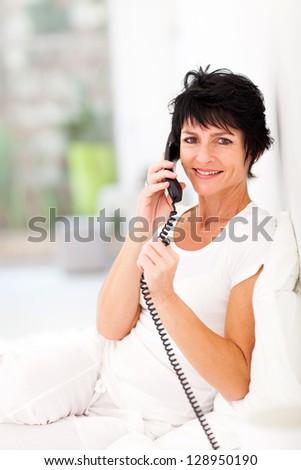 happy mid aged woman talking on landline phone - stock photo