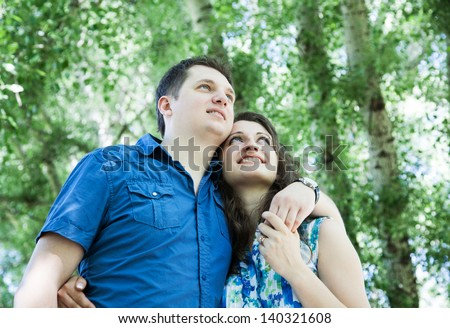 happy middle-age couple in park looking up with hope - stock photo