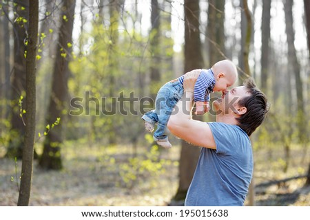 Happy middle age man holding his little baby