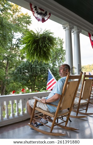 Happy Middle Age Man Sitting On Wooden Rocking Chair At The Terrace And  Viewing The Relaxing