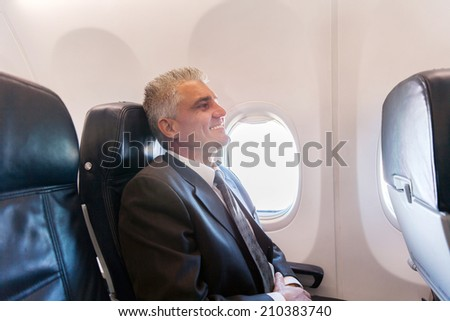 happy middle aged airplane passenger relaxing during flight on air plane  - stock photo