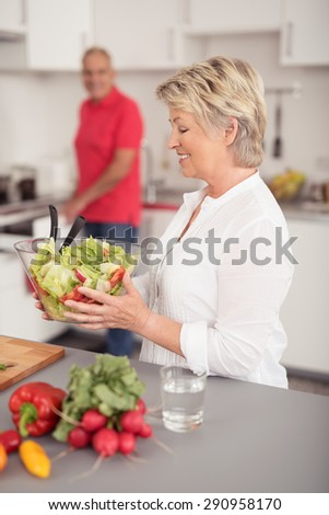Happy Middle Aged Blond Wife Holding Fresh Vegetable Salad in a Bowl Prepared by her Husband at the Kitchen. - stock photo