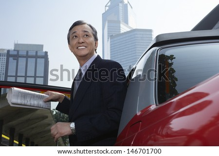 Happy middle aged businessman disembarking from cab - stock photo