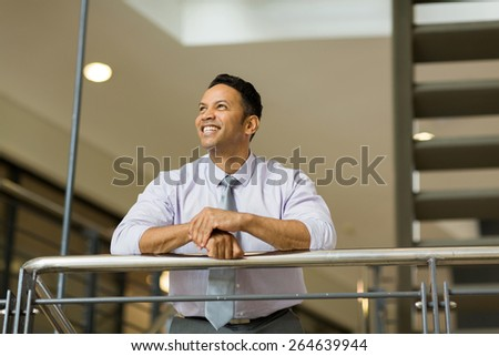 happy middle aged businessman looking up in office - stock photo