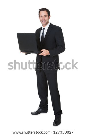 Happy middle aged businessman with laptop. Isolated on white