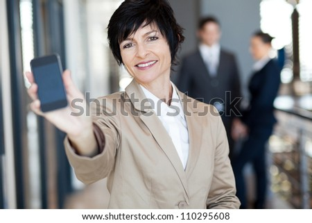 happy middle aged businesswoman showing smart phone - stock photo