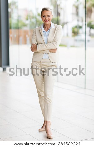 happy middle aged businesswoman standing in office - stock photo