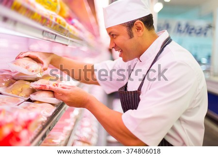 happy middle aged butcher working in butchery  - stock photo