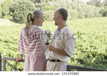 Happy middle aged couple holding wine glasses in front of vineyard - stock photo
