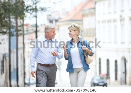Happy middle-aged couple looking at each other while holding ice cream cones in city - stock photo