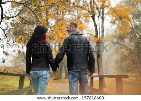 Happy middle-aged couple outdoors on beautiful autumn day - stock photo