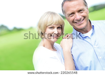 Happy middle aged couple posing together at outdoors