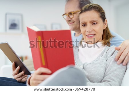 Happy middle-aged couple relaxing at home in a loving embrace on the sofa with the lady reading a book and the man his tablet computer, focus to the woman