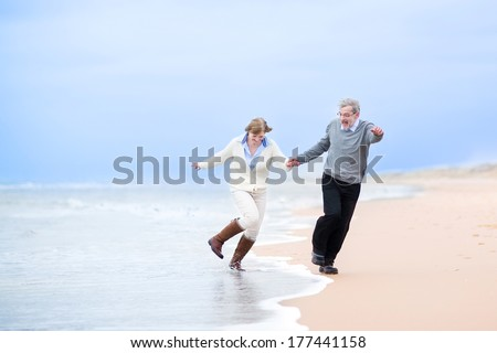 Happy middle aged couple running on a beach holding hands and jumping away from the waves - stock photo