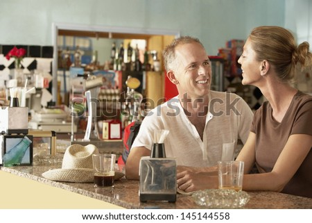 Happy middle aged couple sitting in bar - stock photo