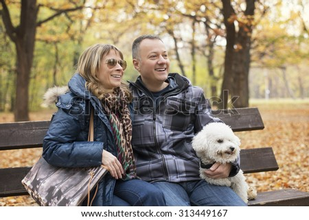 Happy middle aged couple sitting on park bench with their dog and smiling.